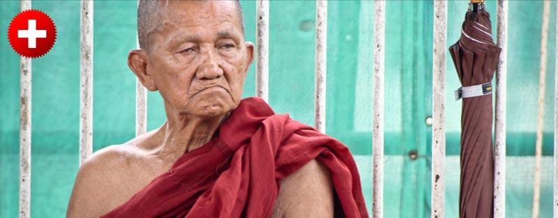 Manih sedi na cesti v Yangonu. Burma (Myanmar) je budistična država zato so menihi na ulicah pogosti.