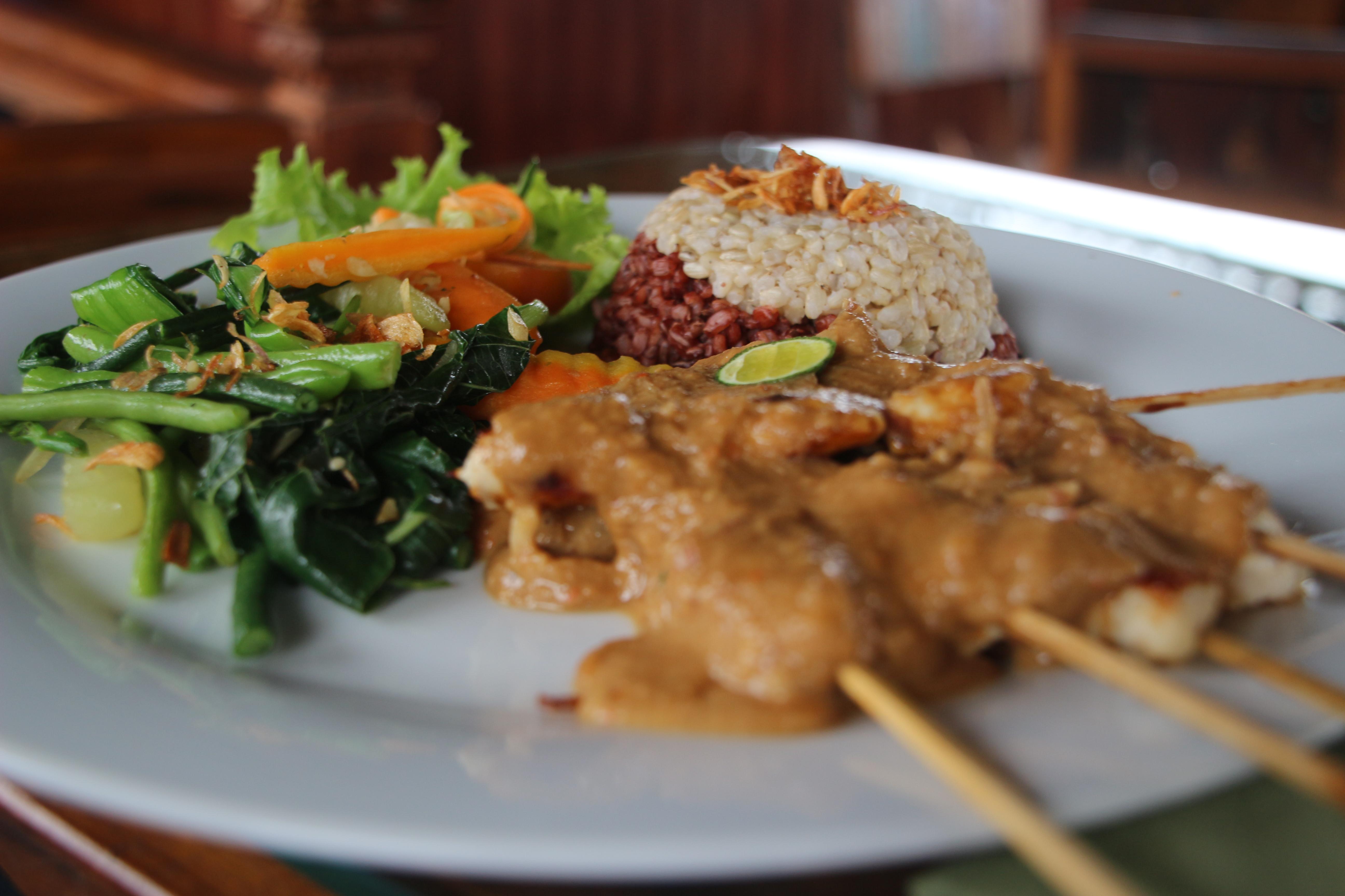 Piščančja nabodala z arašidovo omako, zelenjavo in dvobarvnim rižem.